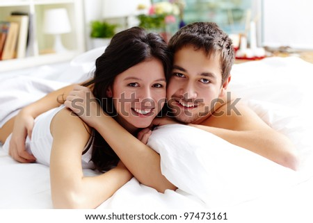 Happy young couple lying in bed and looking at camera