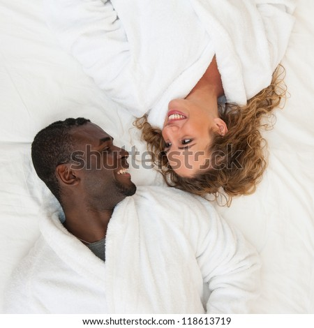 Happy young couple lying in bed looking at each other, top view. - stock photo