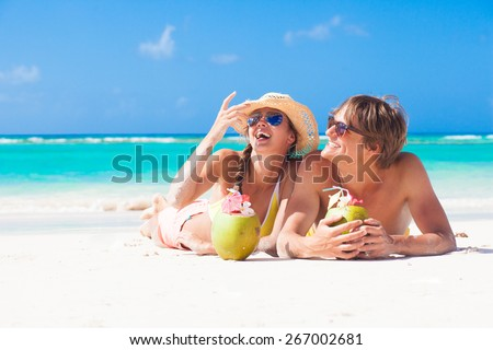 happy young couple lying on a tropical beach in Barbados and drinking a coconut cocktail - stock photo