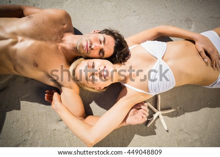 Happy young couple lying on beach