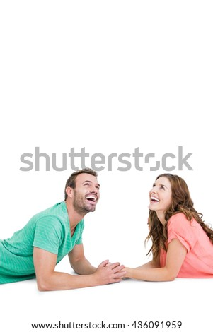Happy young couple lying on floor looking up on white background