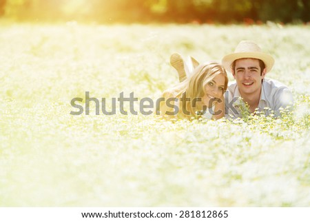 Happy, young couple lying on front in a chamomile, daisy field.Copy space, lens flare - stock photo