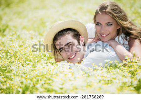 Happy, young couple lying on front in chamomile, daisy field. Copy space. - stock photo