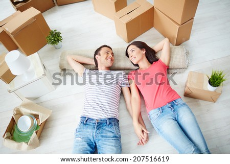 Happy young couple lying on the floor of new house and looking at one another - stock photo