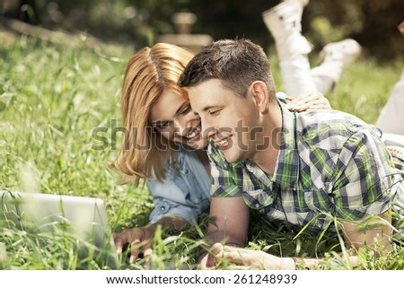 Happy young couple lying on the grass, looking at laptop and smiling. Relationship concept. - stock photo