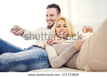 Happy young couple lying on the sofa at home with popcorn watching TV - stock photo