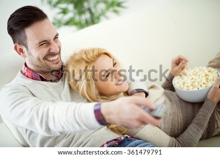 Happy young couple lying on the sofa at home with popcorn watching TV. They are laughing and watching a movie or television. - stock photo