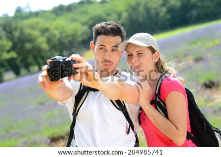 happy young couple making a selfie with camera in countryside during summer holiday trekking - stock photo