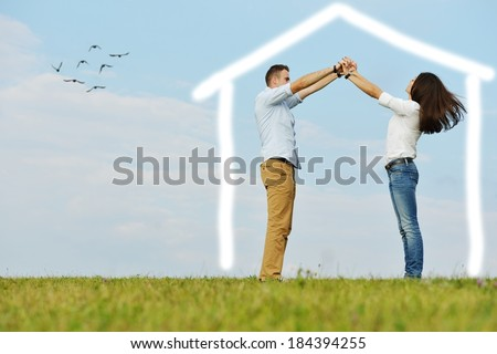 Happy young couple making new illustrated home - stock photo