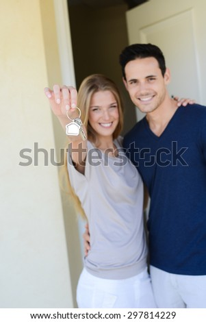 happy young couple man and woman handing over their new home keys in front of open house door - stock photo