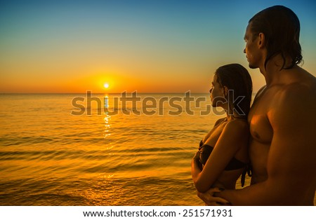Happy young couple meets sunset on a tropical beach - stock photo