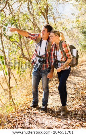 happy young couple mountain climbing together - stock photo