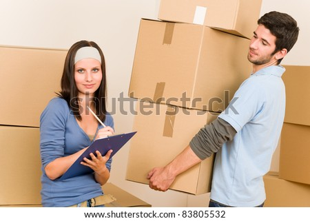 Happy young couple moving into new home carrying cardboard boxes