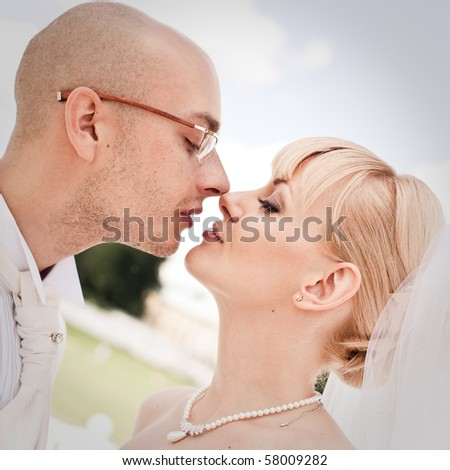 Happy young couple of bride and groom kissing in park