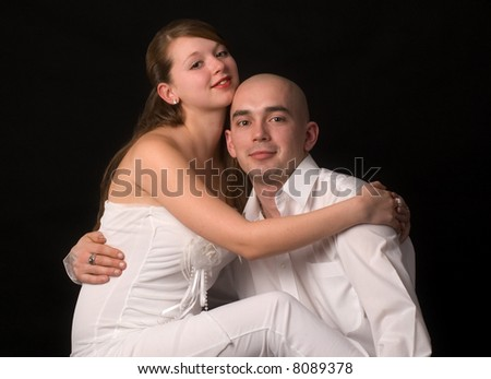 Happy young couple,on a black background.