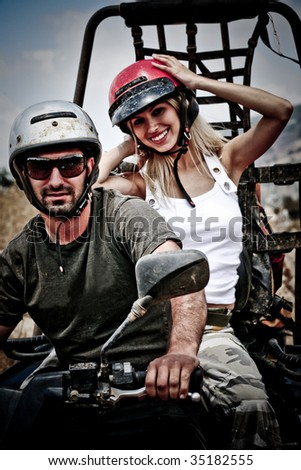 Happy young couple on ATV - stock photo