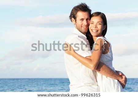 Happy young couple on beach in love embracing and hugging smiling joyful. Interracial young couple, Asian woman, Caucasian man. - stock photo