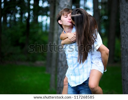 Happy young couple on picnic kissing in park - stock photo