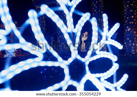 happy young couple on the background illumination of snowflakes. - stock photo