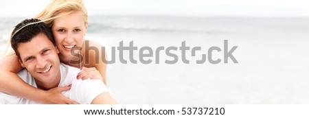 Happy young couple on the beach. Shallow DoF with focus on the man.