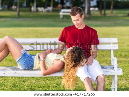 Happy young couple on the bench in park, the girl is lying in her boyfriend's lap - stock photo
