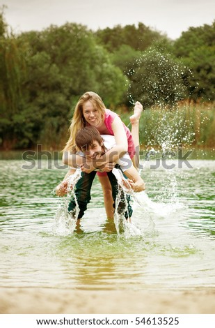 Happy young couple on the lake - stock photo