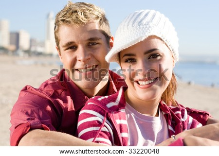 happy young couple on winter beach
