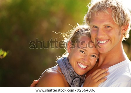 Happy young couple outdoors. Shallow DoF with focus on man. - stock photo