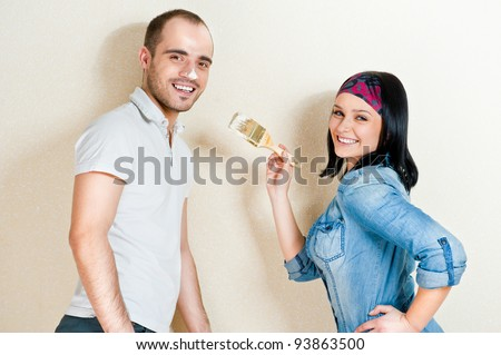 Happy young couple painting their house - stock photo