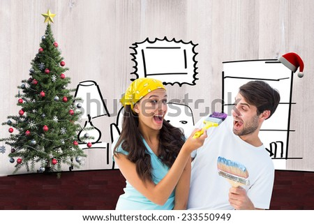 Happy young couple painting together and laughing against living room sketch at christmas - stock photo