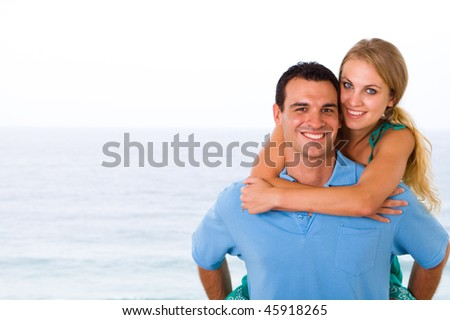 happy young couple piggyback, background is beautiful ocean view