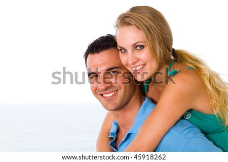 happy young couple piggyback with beautiful sea view behind - stock photo
