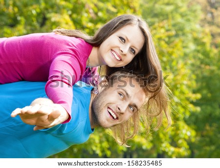 happy young couple piggybacking, arms outstretched, smiling.