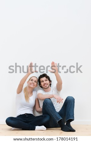 Happy young couple plan their new decor as they sit on the bare wooden floor in their new home pointing and visualizing the placement of their belongings - stock photo