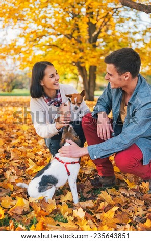 Happy young couple playing with dogs outdoors in autumn - stock photo