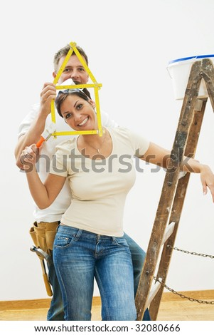 Happy young couple playing with ruler during home improvement. - stock photo