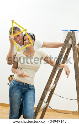 Happy young couple playing with ruler while improving their new home. - stock photo