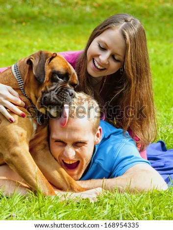 Happy Young Couple Playing with their Dog in the Park. - stock photo