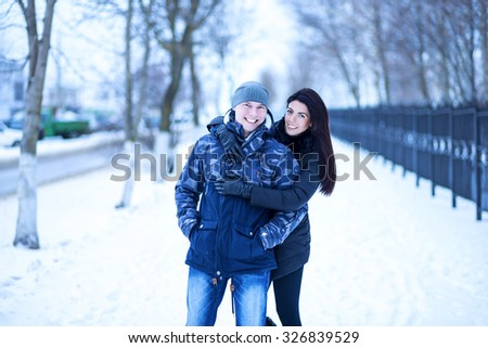 Happy young couple posing close up, smiling young family hugging in the fresh winter air, wearing gloves and a winter jacket. Happy relationships and hugs. The pleasure of love. - stock photo