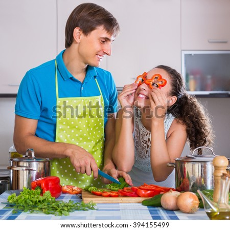 Happy young couple preparing dinner with vegetables and having fun at kitchen