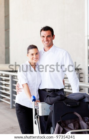 happy young couple pushing luggage at airport
