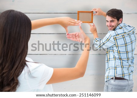 Happy young couple putting up picture frame against painted blue wooden planks - stock photo