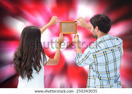 Happy young couple putting up picture frame against valentines heart pattern - stock photo