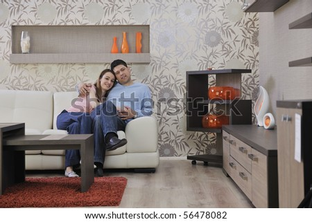 happy young couple relax at home in modern and bright living room - stock photo