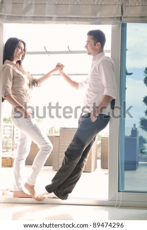 happy young couple relax on balcony outdoor with ocean and blue sky in background - stock photo