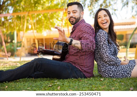 Happy young couple relaxing at a park and having fun with a guitar - stock photo