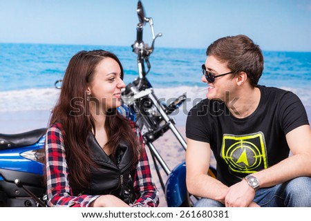 Happy young couple relaxing at the seaside sitting in front of their blue motorbike as they laugh and chat in the summer sun - stock photo