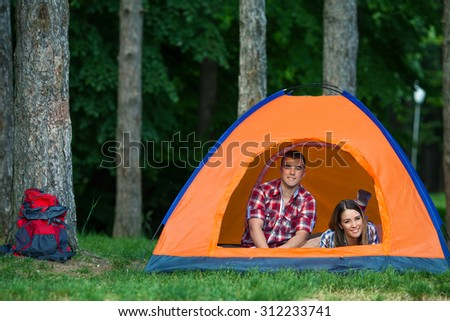 Happy young couple relaxing in a tent while camping in a forest