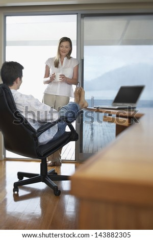 Happy young couple relaxing in home office