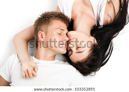 Happy young couple relaxing together while laying over white background - stock photo